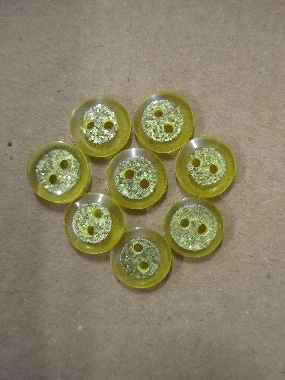 Gul knapp med glitter. Två hål. Storlek 12 mm.