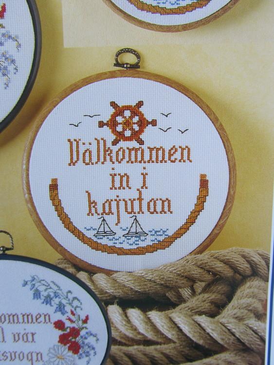 """Korsstygnstavla för båtägaren med texten"""" Välkommen in i kajutan""""."""