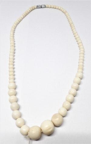 Kort halsband med kulor av ben i olika storlekar