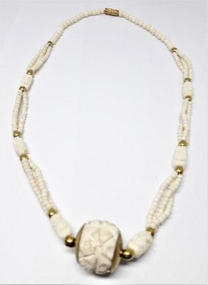 Halsband i ben med kulor i gul metall