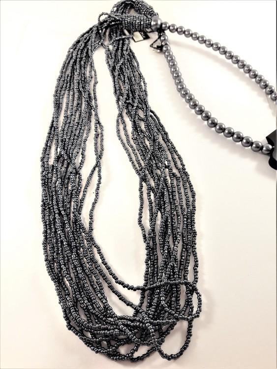 Långt halsband med stora och små pärlor i grått