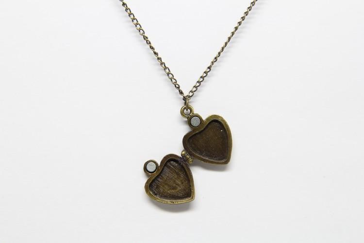 Söt guldfärgad medaljong i kedja och öppningsbart hjärta