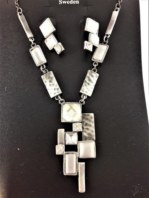 Halskedja med silverfärgade och detaljer och stenar samt matchande örhängen