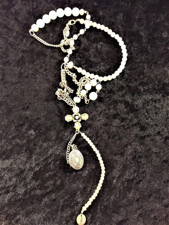 Långt halsband med många olika detaljer i silverfärg