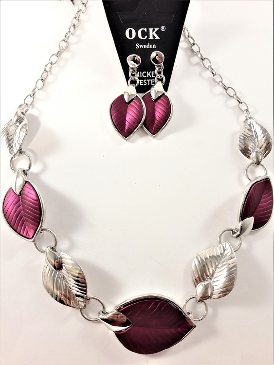Silverfärgad halskedja med detaljer, löv i lila och silverfärg och matchande örhänge