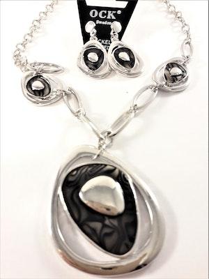 Silverfärgad halskedja med svarta detaljer samt matchande örhängen