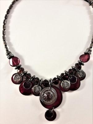 Detaljrikt halsband med många detaljer i lila och silverfärg