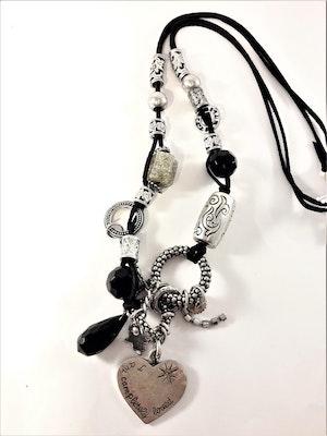 Halsband med silverfärgade och svarta detaljer såsom hjärta