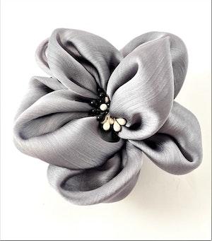 Fin grå hårsnodd med dekorativa pistiller i svart och vitt