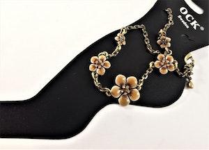 Fotlänk med gnistrande stenar och fina bruna blommor, guldfärgad kedja