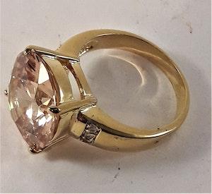 Guldfärgad ring med stor rosa gnistrande sten