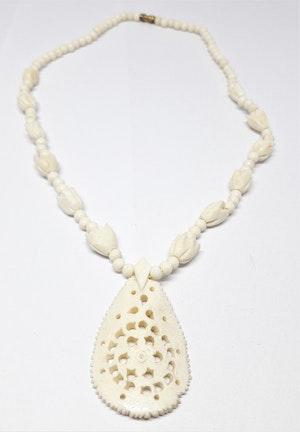 Halsband av ben med blommor och genombrutet hänge