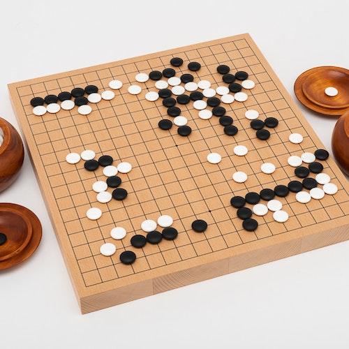 Go-spel, tjockt bräde i bokfanér, träskålar och snäckskalsstenar