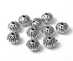 Antikfärgade metallpärlor fint mönstrade 7 mm, ca 100 st