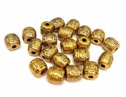 Antikt guldfärgade små mönstrade tunnor, ca 100 st