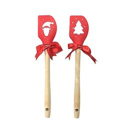 Julslickepott i silikon med trähandtag. Färg: Röd med ett grantryck i vitt.