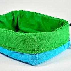 Förvaringskorg i tyg med stoppning, vändbar. Färg: Grön och blå.