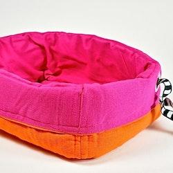 Förvaringskorg i tyg med stoppning, vändbar. Färg: Rosa och orange.