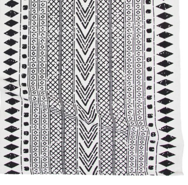 Etnisk en bomullsmatta med tryck. Färg: Vit med ett svart tryckt mönster.