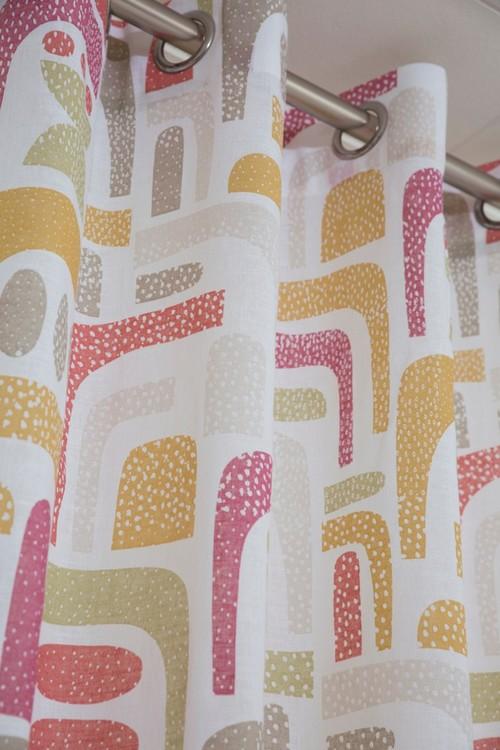 Design ett gardinset med öljetter. Färg: Vit med ett tryck i rosa, röda, gula beiga färger.