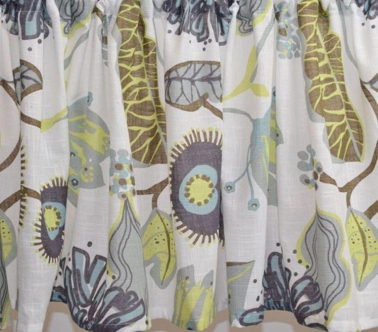 Julia 2 ett färdigsytt gardinset med öljetter. Färg: Vit med ett tryck i grått, brunt, lime och turkos.