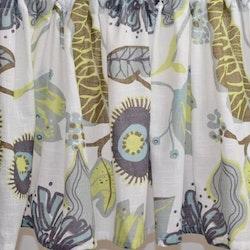Julia 2 en färdigsydd gardinkappa på metervara med öljetter. Färg: Vit med ett tryck i grått, brunt, lime och turkos.