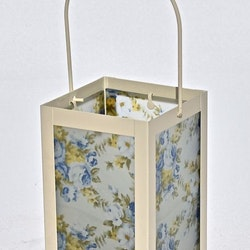 Lykta Blå rosor. Färg: En cremefärgad lykta med vitt glas med blå rosor och gröna blad.