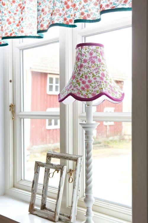 Doris en lampskärm från Boel & Jan med vågad kant. Färg: Vit med aprikos och gula blommor med gröna blad och gröna kantband.