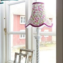 Doris en lampskärm från Boel & Jan med vågad kant. Färg: Vit med prickar i grönt, aprikos och rött med gröna kantband.
