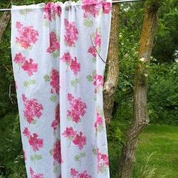 Pelargonia ett gardinset med kanaler från Noble house. Färg: Vit skir väv med rosa pelargonior och gröna blad.