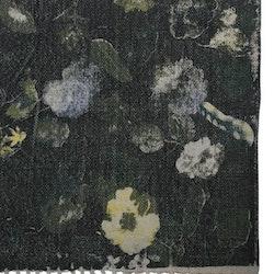 Garden en bomullsmatta med tryckta blommor. Färg: Svart med ett tryckt blommönster i gula och gröna toner.