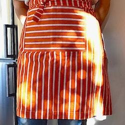 Poppy ett förkläde i bomull från Noble house. Färg: Orange och vitrandigt. Mått: 60 x 75 cm. Material: 100% bomull.