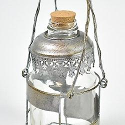 Gammaldags mjölkflaska med metallhållare och kork. Färg: Metall och glas.