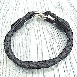 Armband med ett dubbelt flätat läderband och en karbinhake i stål. Art.nr 2023. Färg: Svart och stål.