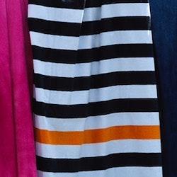 Badlakan i frotté. Färg: Vitt och orange randigt badlakan med en rosa rand. Mått 90 x 150 cm. Material: Bomull.