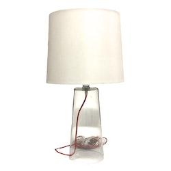 Lampa med glasfot och skärm med en röd tygsladd från Serholt. Färg: Lampfoten är i glas med en vit lampskärm och en röd tygsladd.