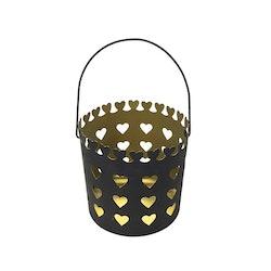 Ljuslykta i metall med ett hjärtmönster, storlek mellan. Färg: Mattsvart utsida och guldfärgad insida.