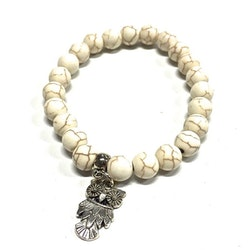 Armband med pärlor och en uggleberlock i polystone med elastiskt band. Art.nr: H 02008. Färg: Off-white.