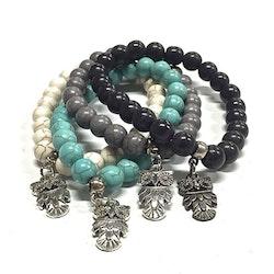 Armband med pärlor och en uggleberlock i polystone med elastiskt band. Art.nr: H 02008. Färg: Aqua.