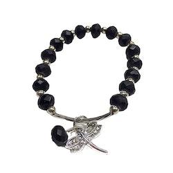 Armband med pärlor i polystone och en metallberlock med en slända. Art.nr: H 02006. Färg: Svart.