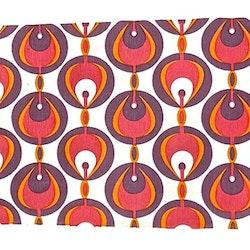 Tablett i bomull med ett retromönster från Noble house. Färg: Vit med ett mönster i rosa, lila och orange..