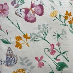 Fjäril är en rund vaxduk från Noble house. Färg: Vit med ett mönster med fjärilar och blommor.