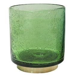 Bubbles en ljuslykta i glas med en fot i mässing. Färg: Grön med en fot i mässing.