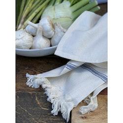 Eslöv en våfflad kökshanduk 100% bomull med fransar. Färg: Off-white med en blå bård.