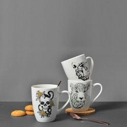 Skulls and snakes en kaffe/te/chokladmugg från Modern house. Färg: Vit med ett tryck i svart och guld.