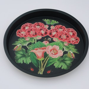 Svart bricka med rosaröda pelargoner och gröna blad