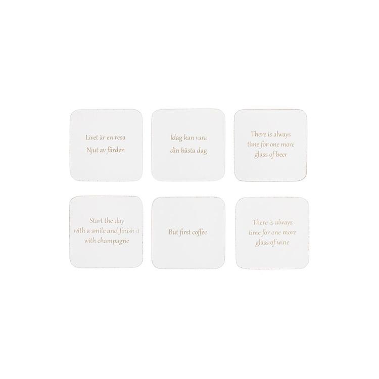 Glasunderlägg med olika texter, i låda