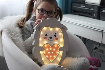 Liten tjej som håller i LED nattlampa för barn
