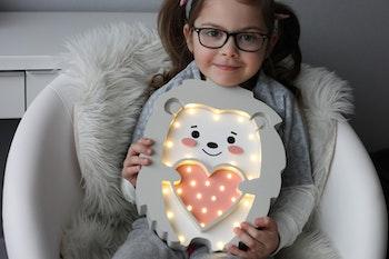 Liten tjej som håller i Igelkott nattlampa för barn