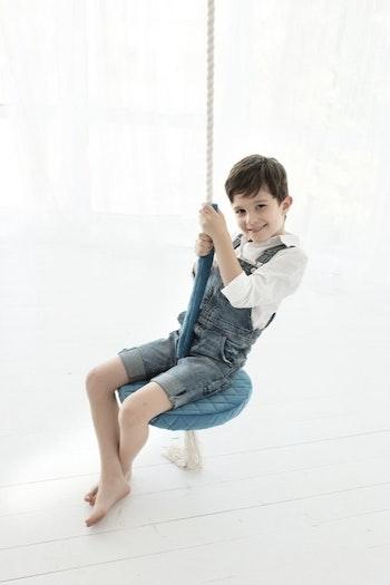 Blå tallriksgunga med en gungande pojke